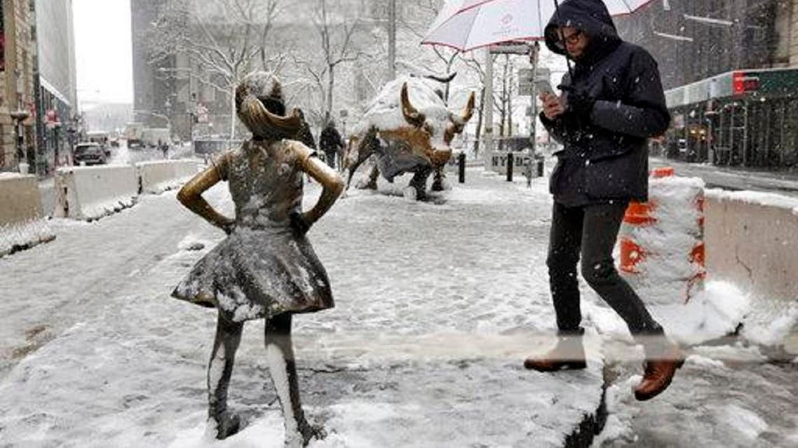 """The """"Fearless Girl"""" and """"Charging Bull"""" sculptures, in New York's Financial District, are covered with snow, on March 21, 2018. (AP)"""