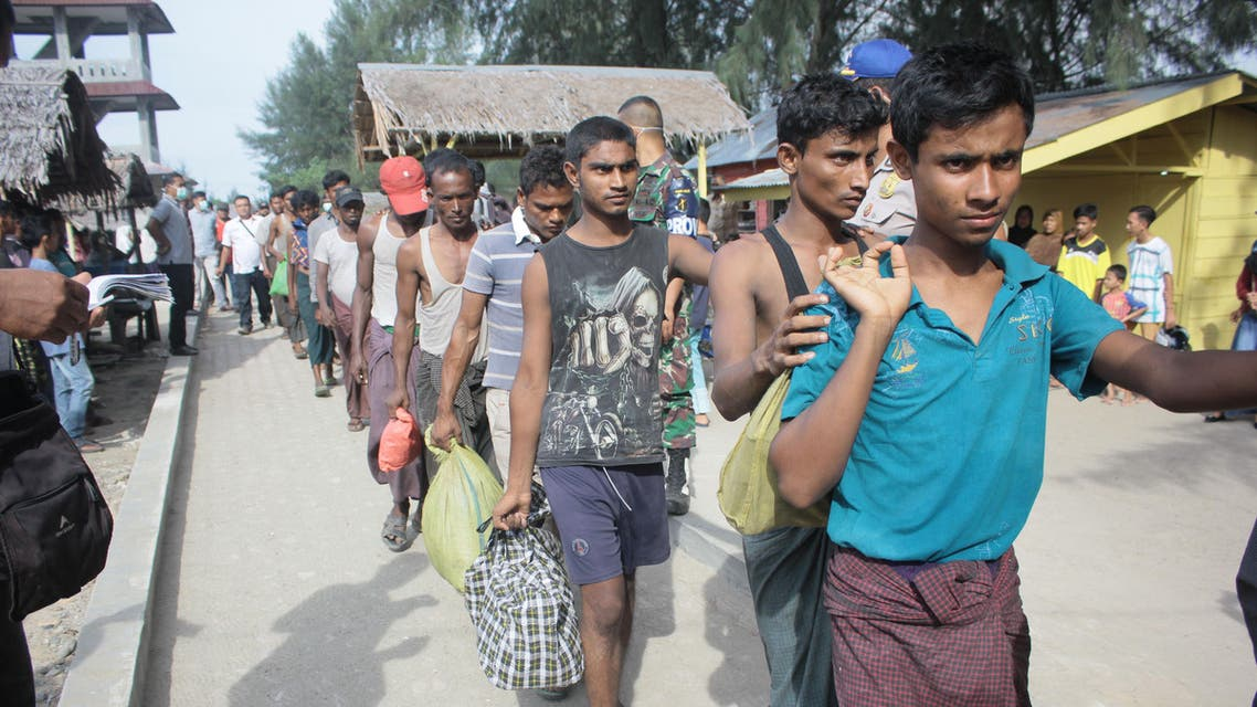 A group of Rohingya refugee make their way to a temporary shelter after landing in Aceh province on Sumatra island on April 20, 2018, just weeks after dozens of the persecuted Muslim minority from Myanmar came ashore in neighbouring Malaysia. About 80 Rohingya in a wooden boat arrived in Indonesia on April 20, officials said, the latest batch of the vulnerable minority to come ashore in the world's biggest Muslim majority nation. Amanda JUFRIAN / AFP