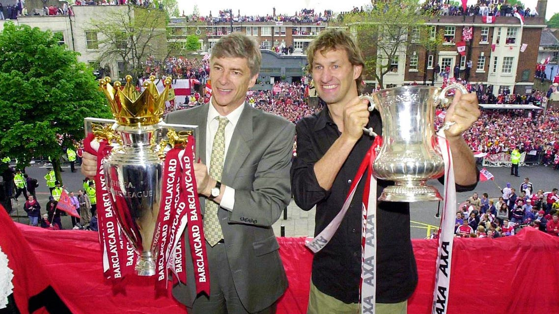 In this May 12, 2002 file photo Arsenal's manager Arsene Wenger, left, and captain Tony Adams proudly hold the Premier League Trophy and FA Cup. (AP)