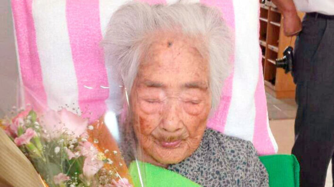 Nabi Tajima, born in 1900, holds a bouquet in Japanese southwestern island of Kikaijima, Kagoshima Prefecture, Japan, in this photo taken in 2015 and released by Kyodo. Mandatory credit Kyodo/via REUTERS ATTENTION EDITORS -THIS IMAGE WAS PROVIDED BY A THIRD PARTY. MANDATORY CREDIT. JAPAN OUT. THIS IMAGE WAS PROCESSED BY REUTERS TO ENHANCE QUALITY, AN UNPROCESSED VERSION HAS BEEN PROVIDED SEPARATELY.