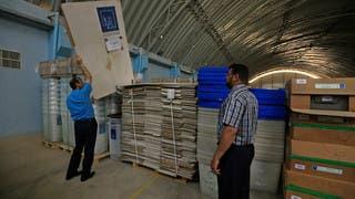 موظفون من هيئة الإشراف على الانتخابات يتفحصون تجهيزات مراكز الاقتراع في النجف