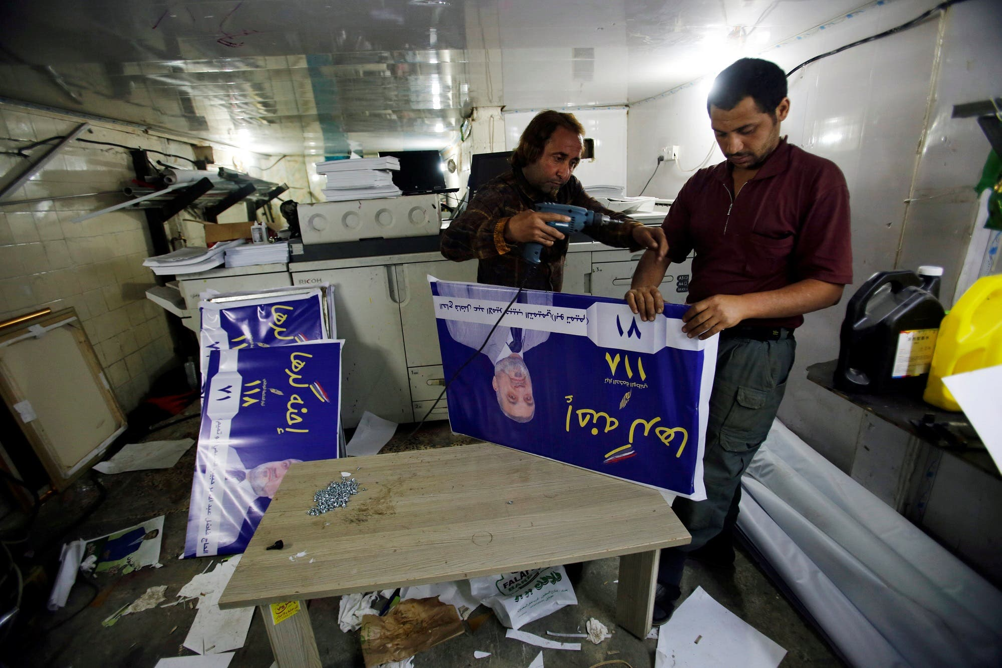 Men work on campaign posters of local candidates ahead of the parliamentary election, in Baghdad on April 14, 2018. (Reuters)