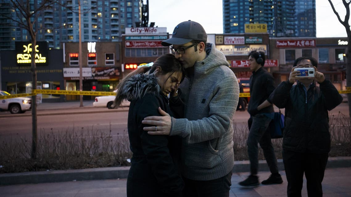 People embrace at the scene of crash on April 23, 2018 in Toronto, Canada. (AFP)