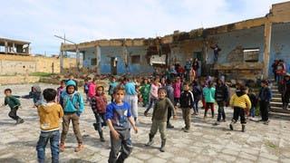 أطفال سوريون يلعبون في فناء مدرسة مدمّرة في إدلب