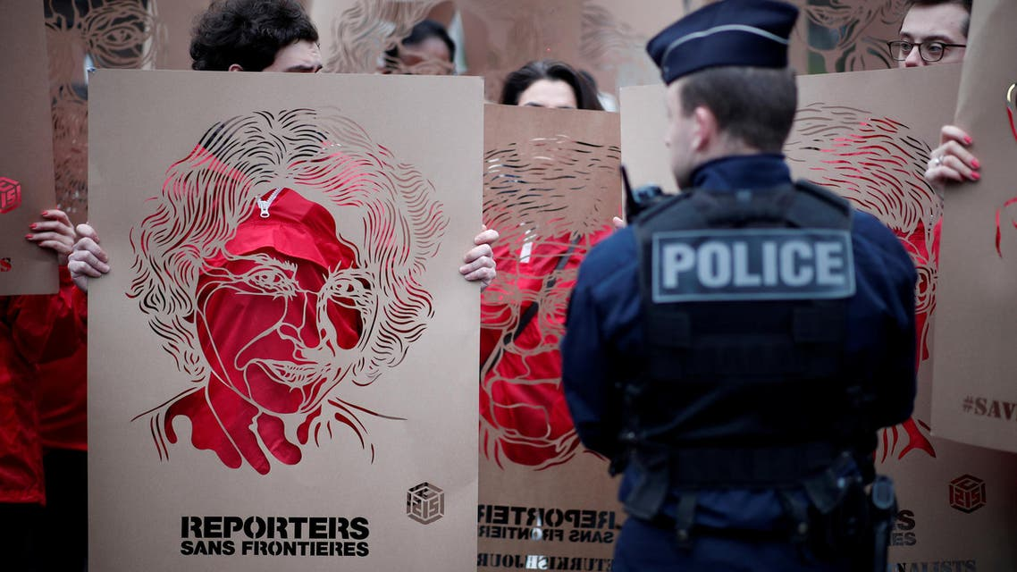 Members of Reporters Without Borders (RSF) hold stencils made by French street artist C215 representing portraits of emprisonned Turkish journalists, as they take part in a demonstration in front of the Turkish embassy in Paris, France, January 5, 2018. (Reuters)