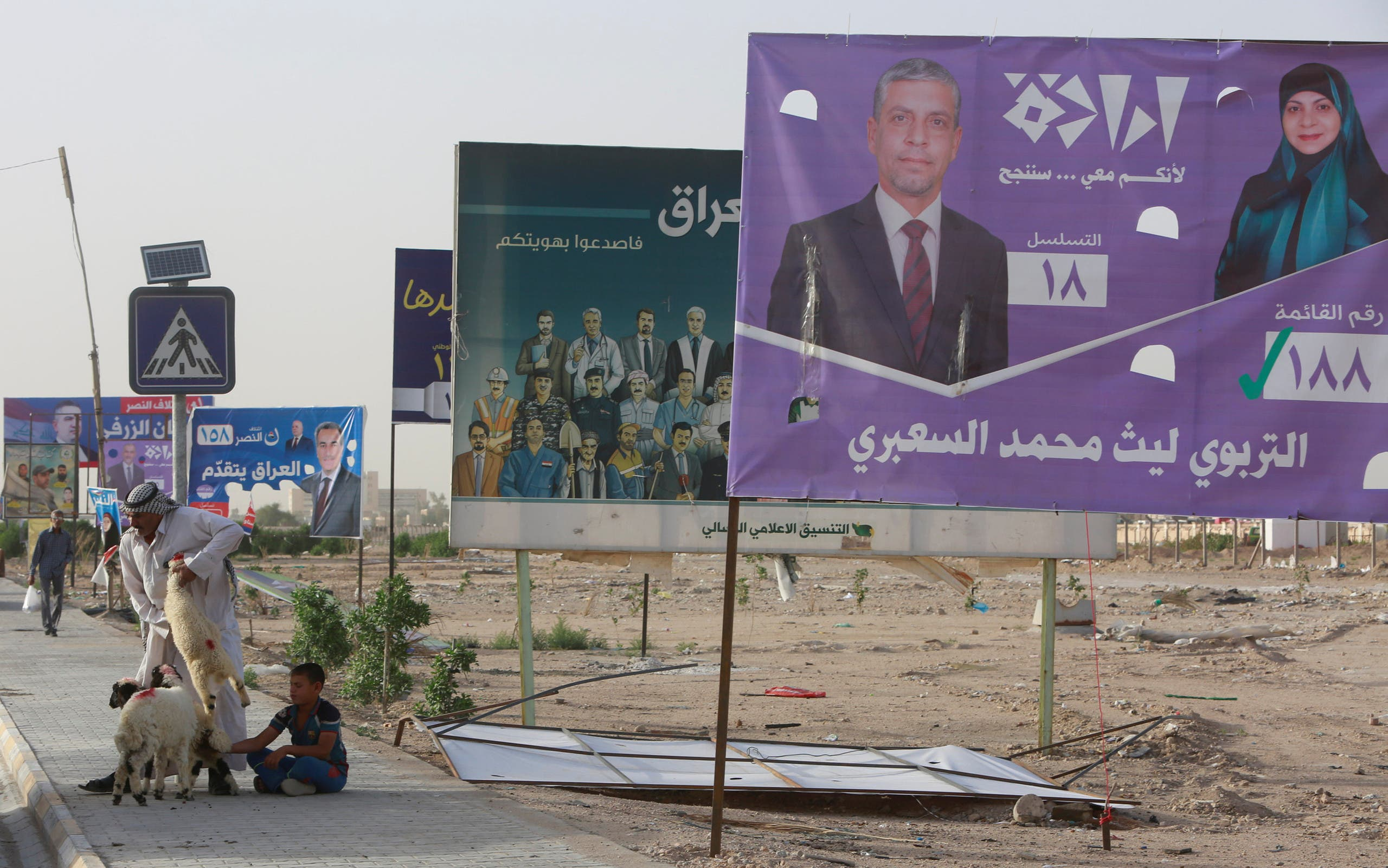 A man holds a sheep for sale next to campaign posters of candidates ahead of parliamentary election, in Iraq, April 20, 2018. (Reuters)