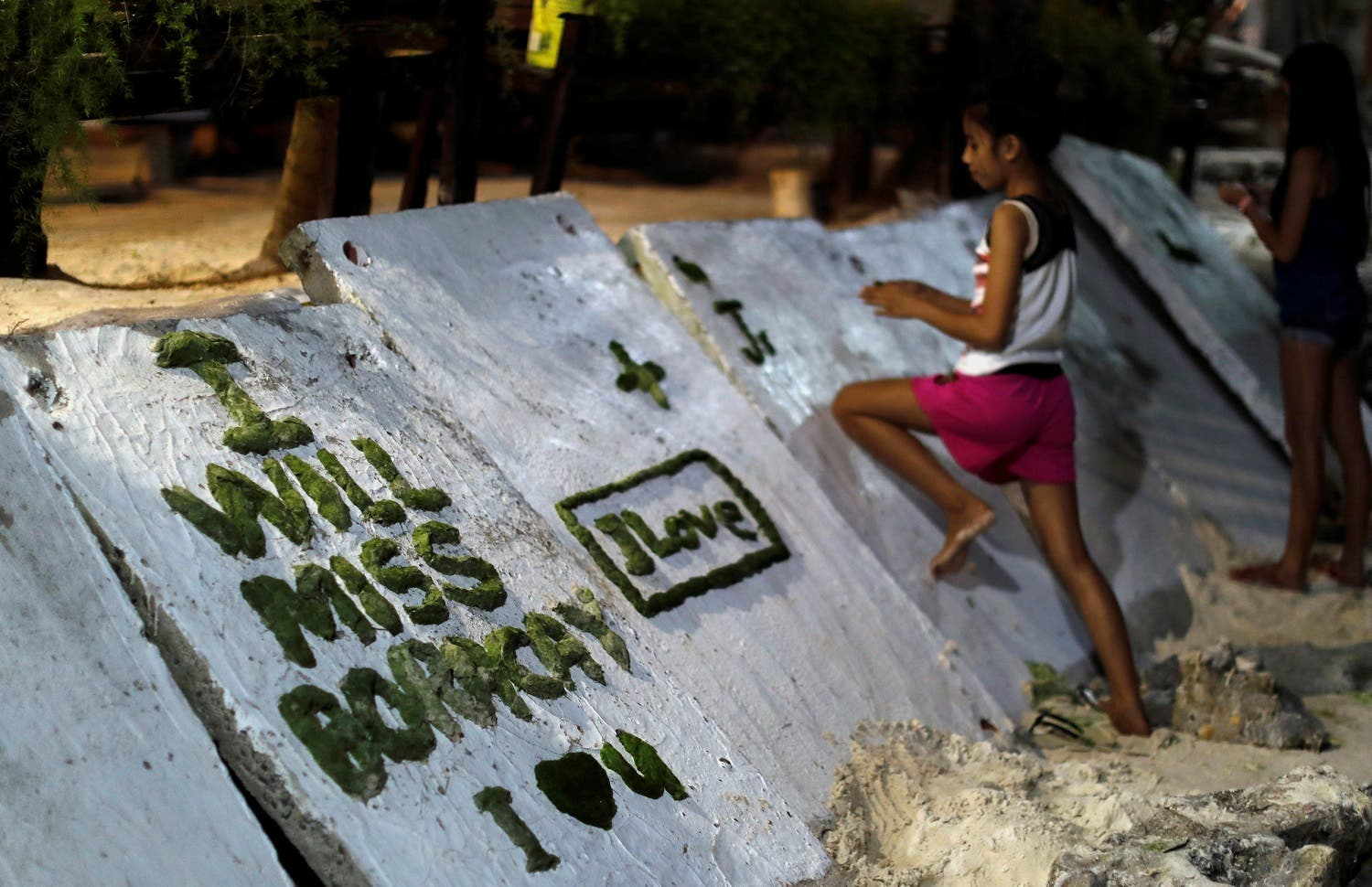 A girl scribbles on a wall two days before the temporary closure of the holiday island Boracay, in the Philippines. (Reuters)