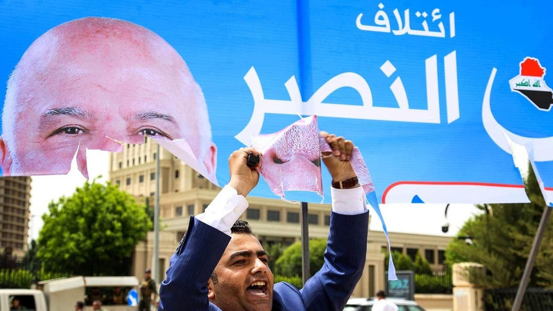 An Iraqi Kurdish man holds up piece he tore from a campaign banner for Iraqi Prime Minister Haider al-Abadi, for the upcoming parliamentary elections in the capital of the northern Iraqi Kurdish autonomous region. (AFP)