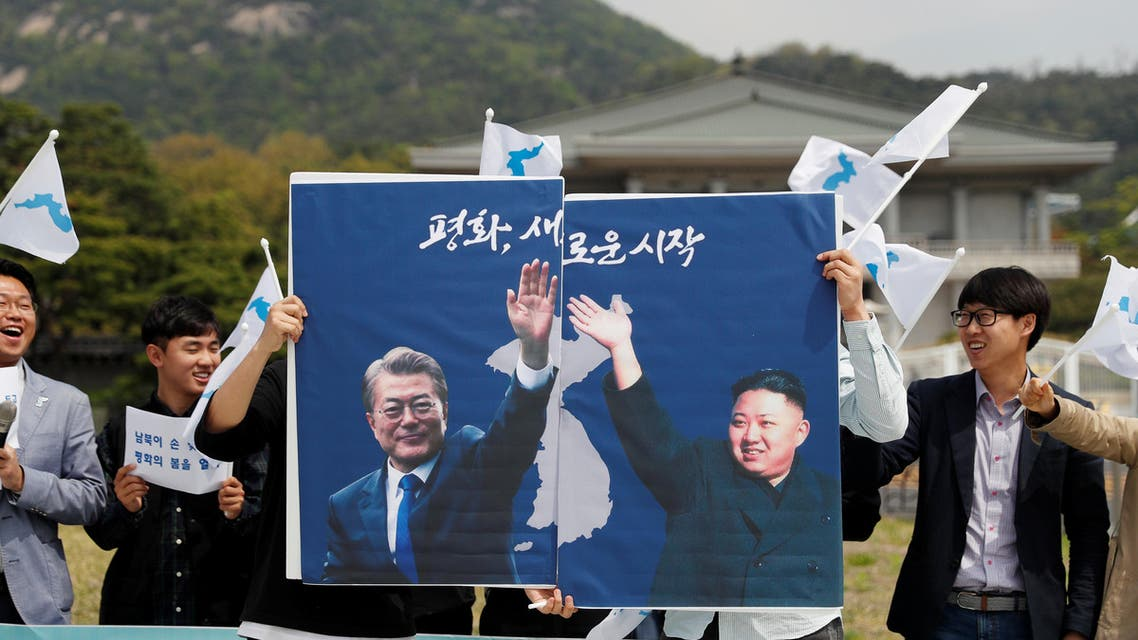 Students hold posters with pictures of South Korea's President Moon Jae-in and North Korea's leader Kim Jong Un during a pro-unification rally ahead of the upcoming summit between North and South Korea in Seoul, South Korea April 26, 2018. REUTERS/Jorge Silva
