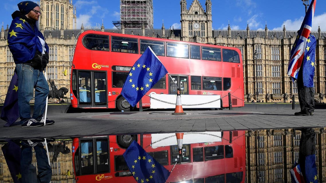 Anti-Brexit demonstrators waving EU and Union flags are reflected in a puddle in front of the Houses of Parliament in London on March 28, 2018. (Reuters)