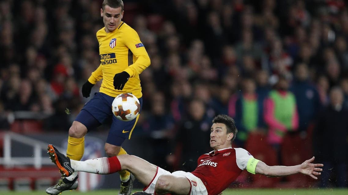 Atletico Madrid's Antoine Griezmann (L) vies with Arsenal's defender Laurent Koscielny on his way to scoring their first goal during the first leg semi-final football match at the Emirates Stadium in London on April 26, 2018. (AFP)
