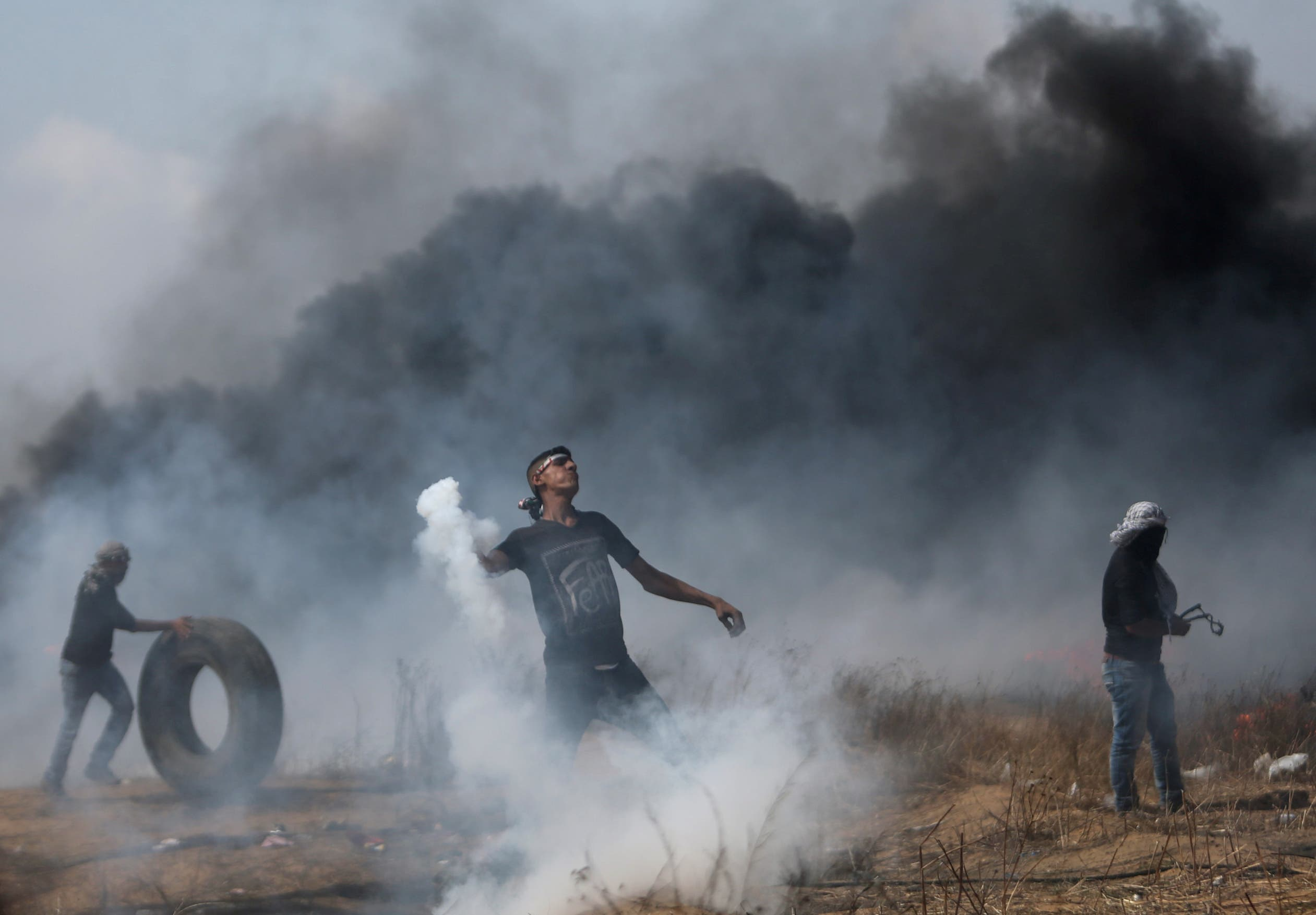A demonstrator hurls back a tear gas canister fired by Israeli troops during clashes at a protest where Palestinians demand the right to return to their homeland, at the Israel-Gaza border in the southern Gaza Strip, April 27, 2018. REUTERS/Ibraheem Abu Mustafa