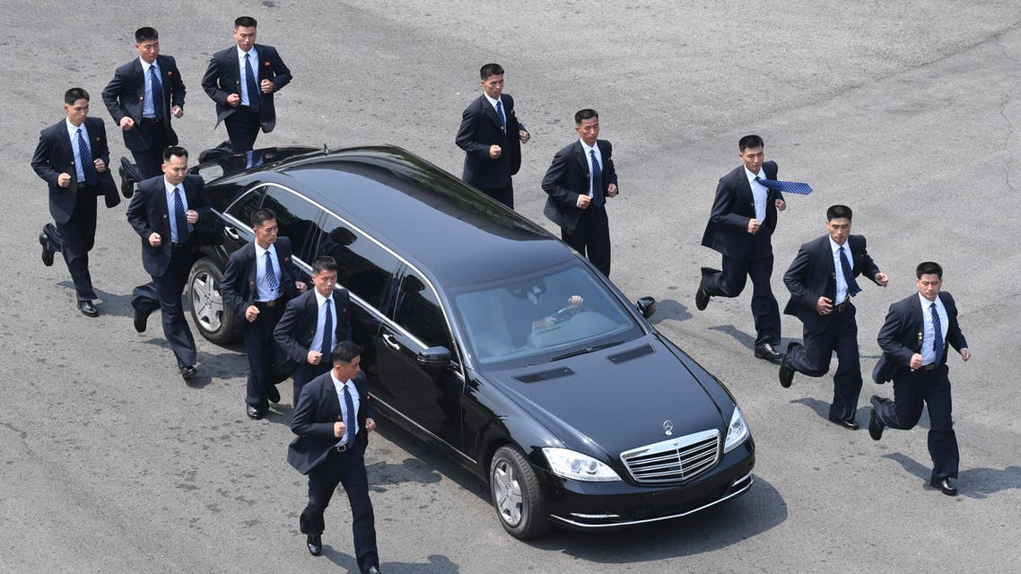 North Korean bodyguards jog next to a car carrying North Korea's leader Kim Jong Un returning to the North for a lunch break after a morning session of the inter-Korean summit at the truce village of Panmunjom on April 27, 2018. North Korean leader Kim Jong Un and the South's President Moon Jae-in sat down to a historic summit on April 27 after shaking hands over the Military Demarcation Line that divides their countries in a gesture laden with symbolism.