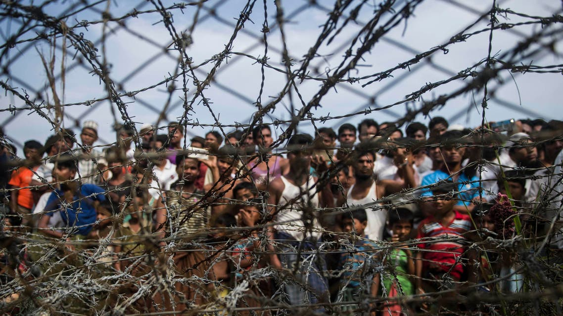 """This picture taken from Maungdaw district, Myanmar's Rakhine state on April 25, 2018 shows Rohingya refugees gathering behind a barbed-wire fence in a temporary settlement setup in a """"no man's land"""" border zone between Myanmar and Bangladesh. A United Nations Security Council delegation which wants to see first-hand the impact of the Rohingya refugee crisis will arrive in Myanmar on April 30 and visit Rakhine state, a senior government official said. Myanmar and Bangladesh signed a repatriation deal for refugees to return in January but so far only one family has returned from a no man's land between the two nations. (AFP)"""