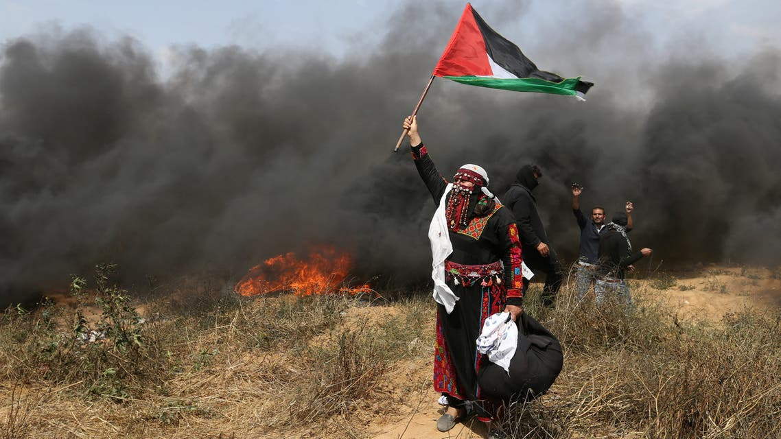 A woman demonstrator holds a Palestinian flag during clashes with Israeli troops at a protest where Palestinians demand the right to return to their homeland, at the Israel-Gaza border in the southern Gaza Strip, April 27, 2018. REUTERS/Ibraheem Abu Mustafa