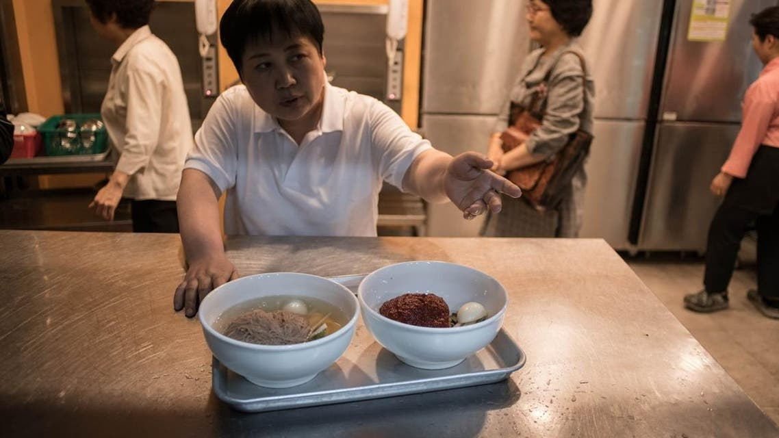 Waiter serves a 'Pyongyang naengmyeon' cold noodle dish at a Seoul noodle bar restaurant. (AFP)