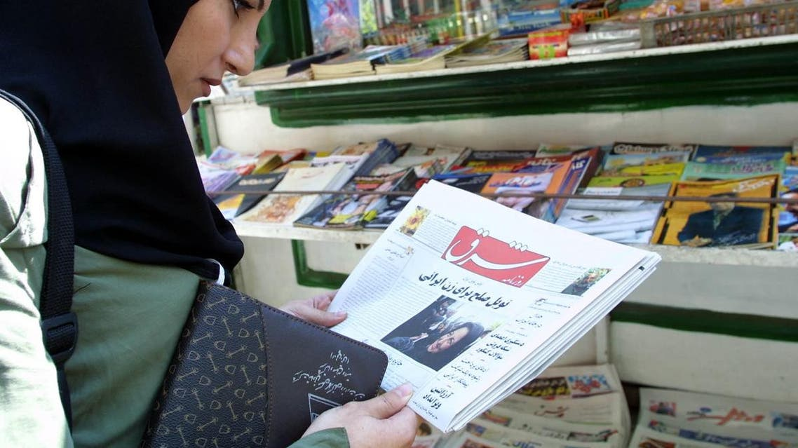 """An Iranian woman looks at the front page of a newspaper at a stall showing the """"Nobel Peace prize for Iranian Woman"""" in the reformist daliy """"Shargh"""" in the center of Tehran. (AFP)"""