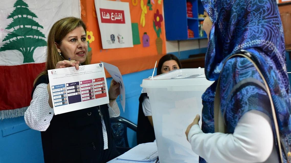 A polling station official explains the voting proceedure to a Lebanese national preparing to cast her ballot in the middle-eastern nations parliamentary election at a polling station set up at the Lebanese School in Abidjan. (AFP)