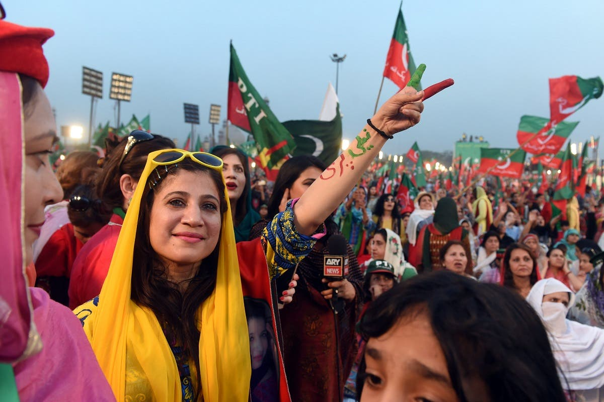 Supporters gesture and wave flags of the Pakistani political party Pakistan Tehreek-e-Insaf (PTI - Pakistan Movement for Justice) as they attend a rally with Pakistan opposition leader and leader of the party, in Lahore. (AFP)