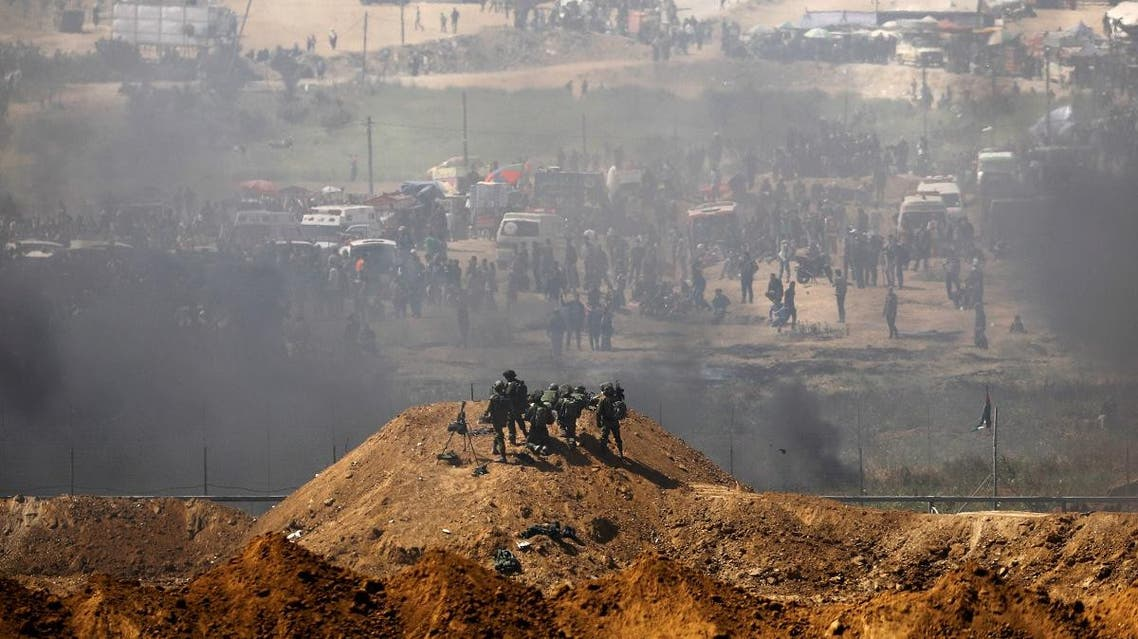 Israeli soldiers are seen next to the border fence on the Israeli side of the Israel-Gaza border. (Reuters)