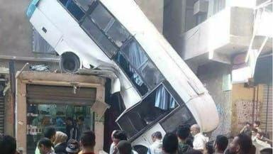 صور صادمة.. حافلة تسقط وتتعلق بركابها فوق منزل بمصر