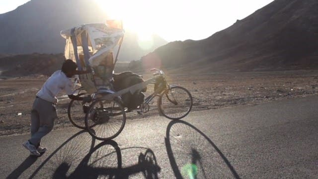 Satyen Das pushing his rickshaw from behind on a slope. (Supplied)