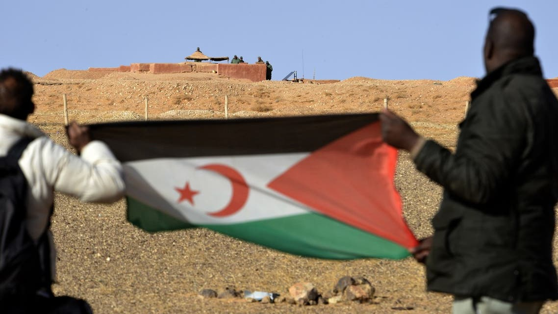 Saharawi men hold up a Polisario Front flag in the Al-Mahbes area near Moroccan soldiers guarding the wall separating the Polisario controlled Western Sahara from Morocco on February 3, 2017. It is the world's oldest functioning security barrier, dubbed a wall of shame and death by Western Sahara residents and leaders who want independence from Morocco.