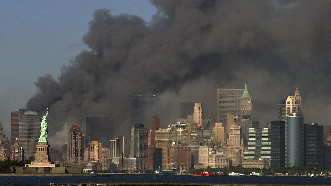 thick smoke billows into the sky from the area behind the Statue of Liberty, lower left, where the World Trade Center towers stood. (AP)