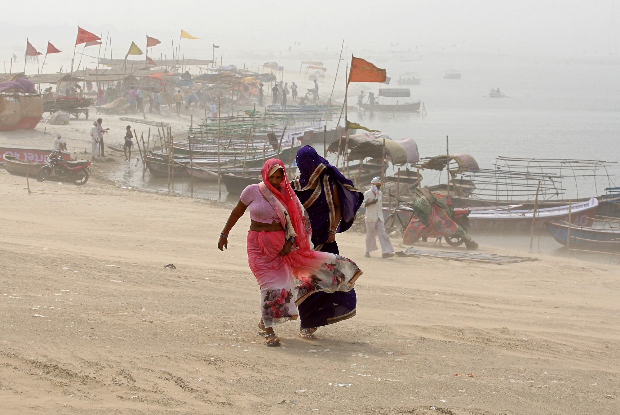 Women cover themselves as they walk on the banks of the river Ganges during a dust storm in Allahabad on April 7, 2018. (Reuters)