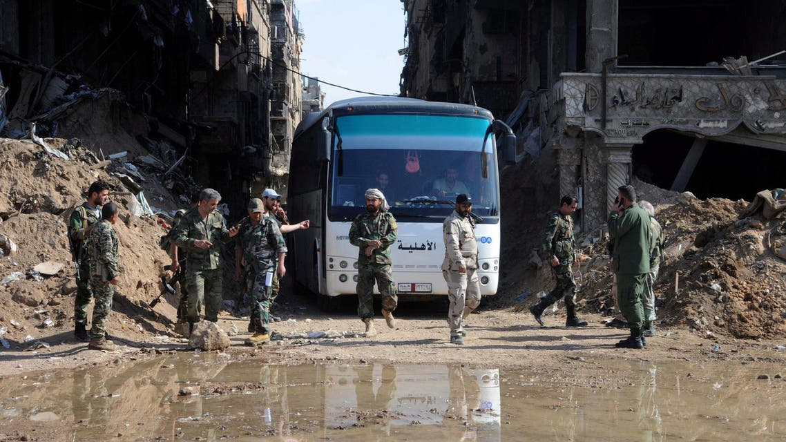 Soldiers loyal to Bashar al Assad seen near a bus carrying rebels from Yarmouk camp in Damascus on April 30, 2018. (Reuters)