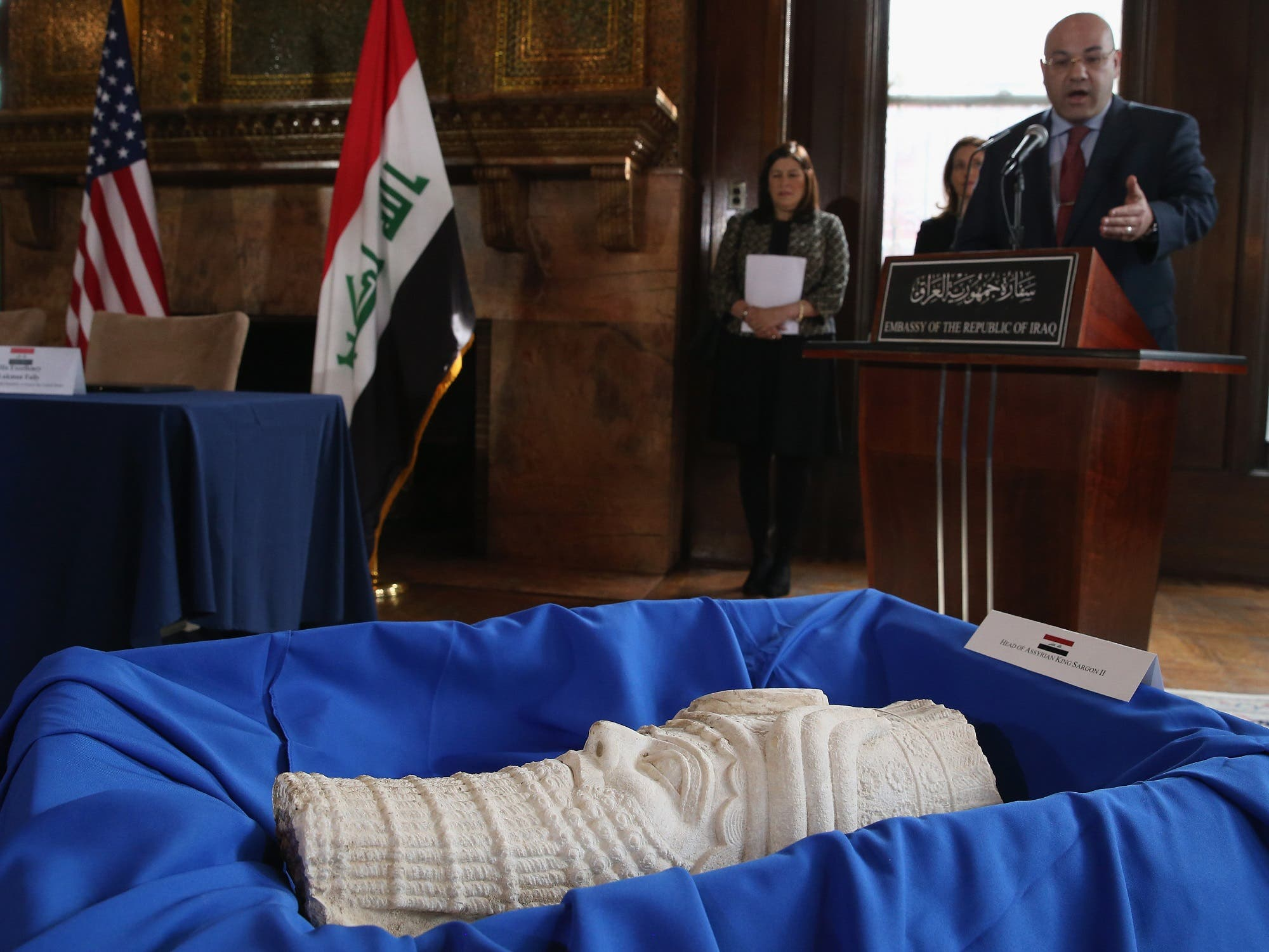 Iraqi Ambassador to the US Lukman Faily speaks in front of a sculpture of the head of Assyrian King Sargon II on March 16, 2015 in Washington, DC. (AFP)