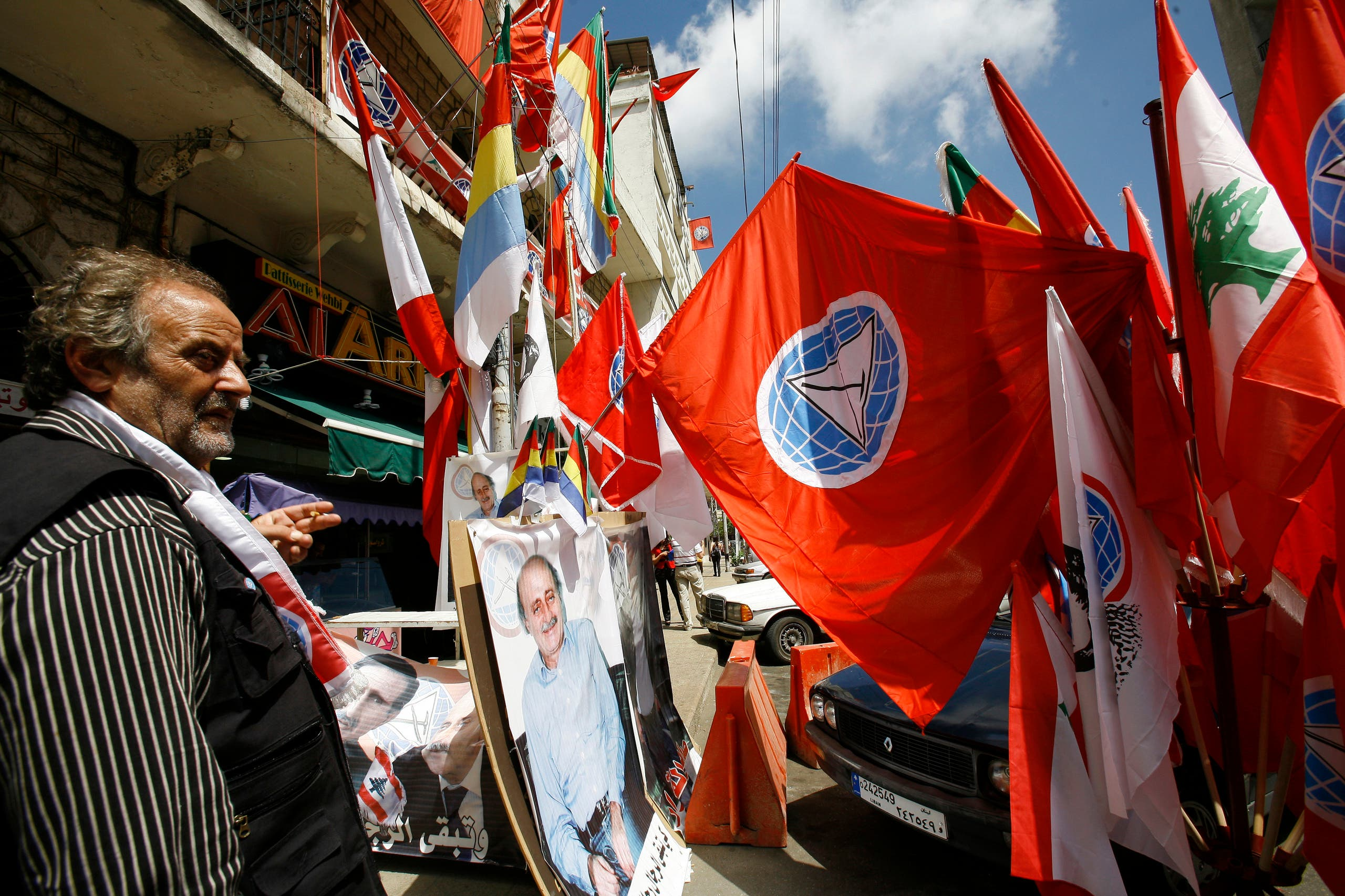 A Lebanese Druze vendor displays Progressive Socialist Party flags and pictures of Druze leader Walid Jumblatt in a street in Aley June 6, 2009. REUTERS/ Jamal Saidi (LEBANON ELECTIONS POLITICS)