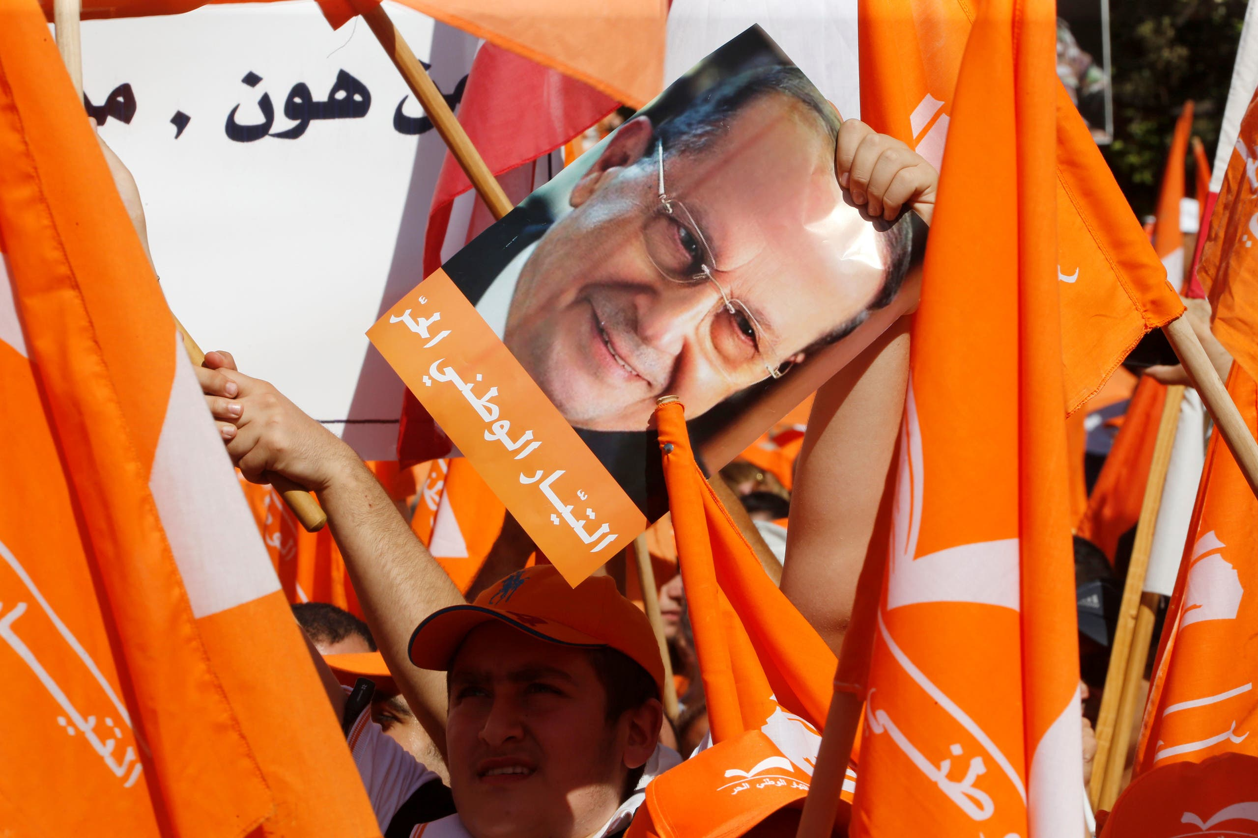 Supporters of the Free Patriotic Movement (FPM) carry flags and a picture of Christian politician and FPM founder Michel Aoun during a rally to show support for Aoun and calling to elect a president, near the presidential palace in Baabda, near Beirut, Lebanon October 16, 2016. REUTERS/Mohamed Azakir