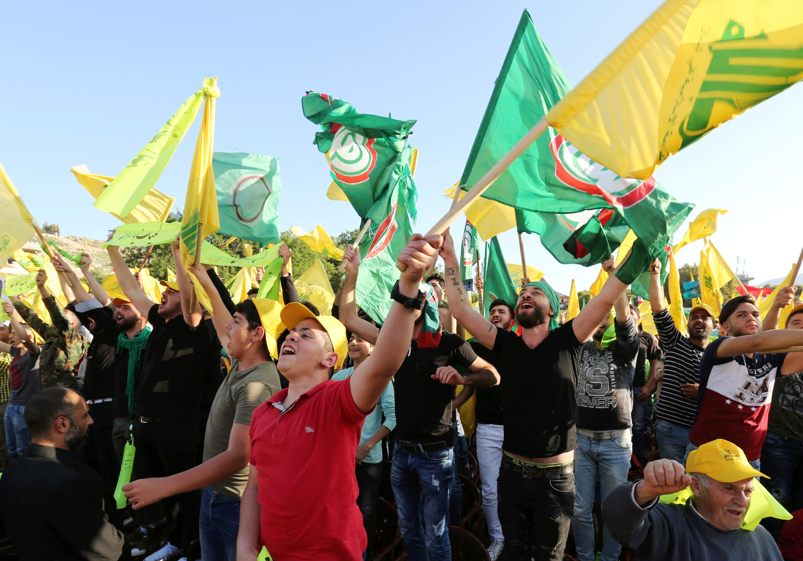 Supporters of Lebanon's Hezbollah chant slogans and hold flags as they listen to their leader Sayyed Hassan Nasrallah during a rally, in Mashghara village in the Bekaa Valley, Lebanon April 15, 2018. REUTERS/Aziz Taher
