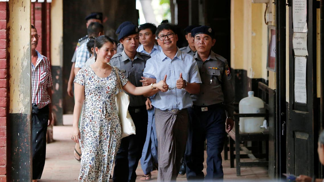 Detained Reuters journalist Wa Lone (C) escorted by police and his wife arrives for a court hearing in Yangon on April 25, 2018. (Reuters)