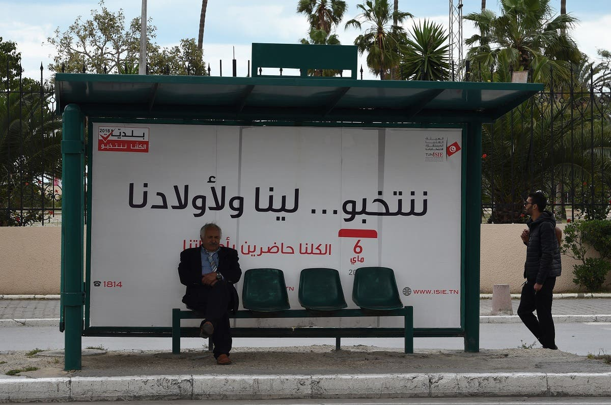 A tunisian man waits for a bus in front of a municipal elections awareness campaign poster in Tunis. (AFP)