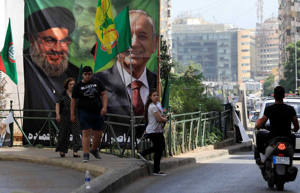 People walk past a campaign banner showing Lebanese Parliament Speaker and candidate for parliamentary election Nabih Berri and Hezbollah leader Sayyed Hassan Nasrallah in Beirut. (Reuters)