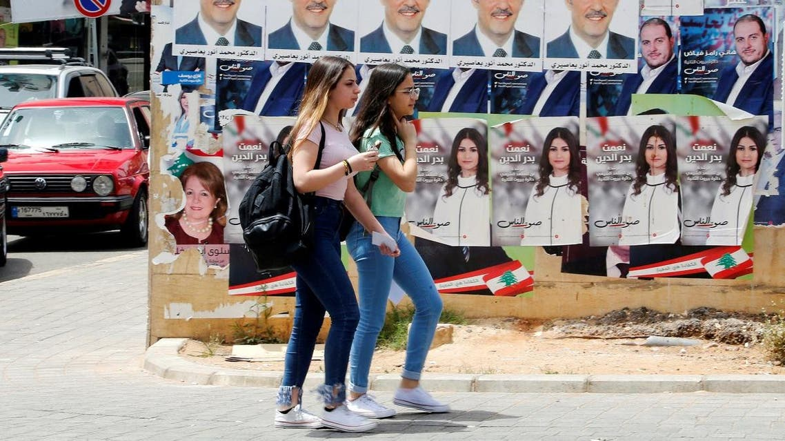 Girls walk past pictures of Lebanese parliament candidates in Beirut. (Reuters)