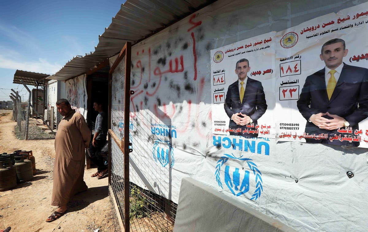 Displaced Iraqis from the former embattled city of Mosul walk near election campaign posters, at the Hasan Sham camp, some 40 kilometres east of Arbil in northern Iraq, on May 1, 2018, two weeks before Iraqis are set to vote in the parliamentary elections. (AFP)