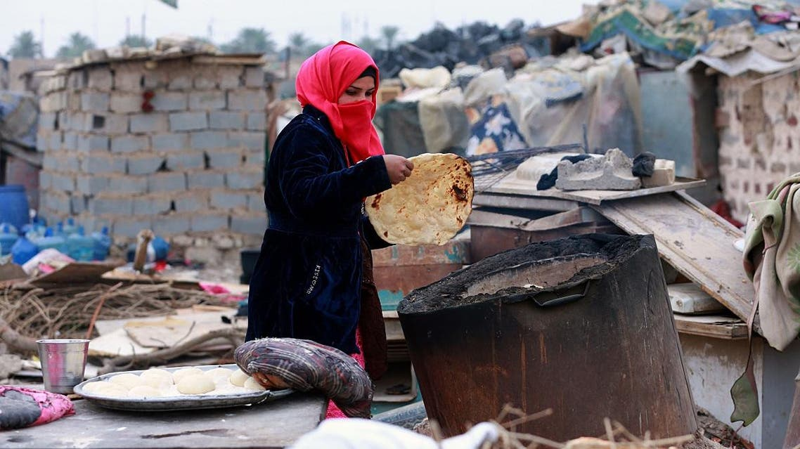 Umm Salem bakes bread in front of her hut at an encampment for the displaced outside Baghdad, Iraq. (AP)