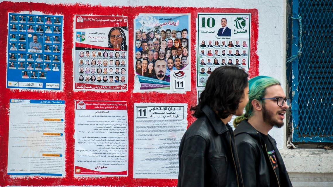People walk past electoral posters in l'Ariana, outside Tunis, Friday, May 4 2018. (AP)