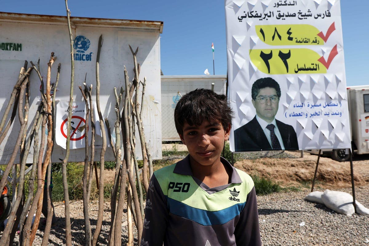 A displaced Iraqi from the former embattled city of Mosul poses for a photo in front of an election campaign poster, at the Hasan Sham camp. (AFP)