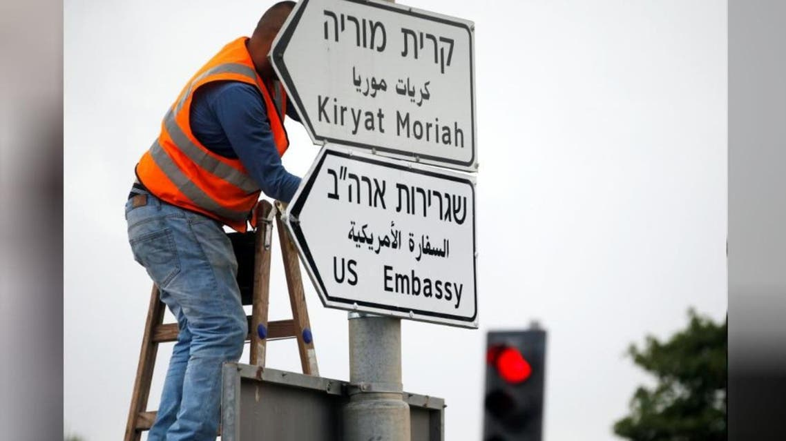 A worker hangs a road sign directing to the U.S. embassy, in the area of the U.S. consulate in Jerusalem, May 7, 2018. (Reuters)