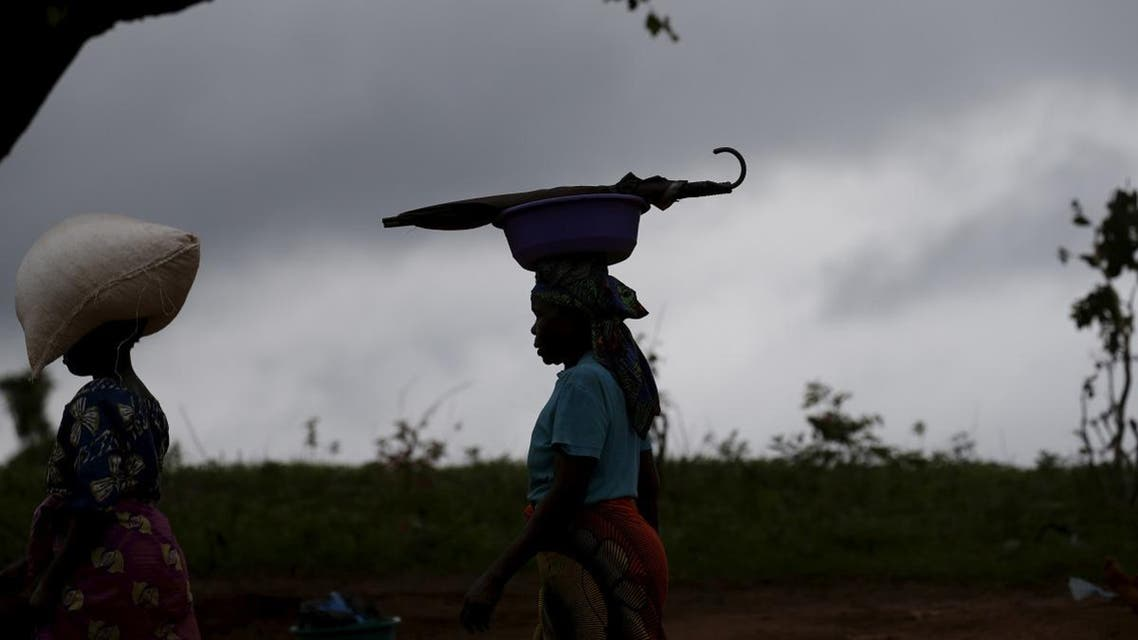 Storm clouds loom as a woman carries maize and an umbrella on her head near Malawi's capital Lilongwe. (Reuters)