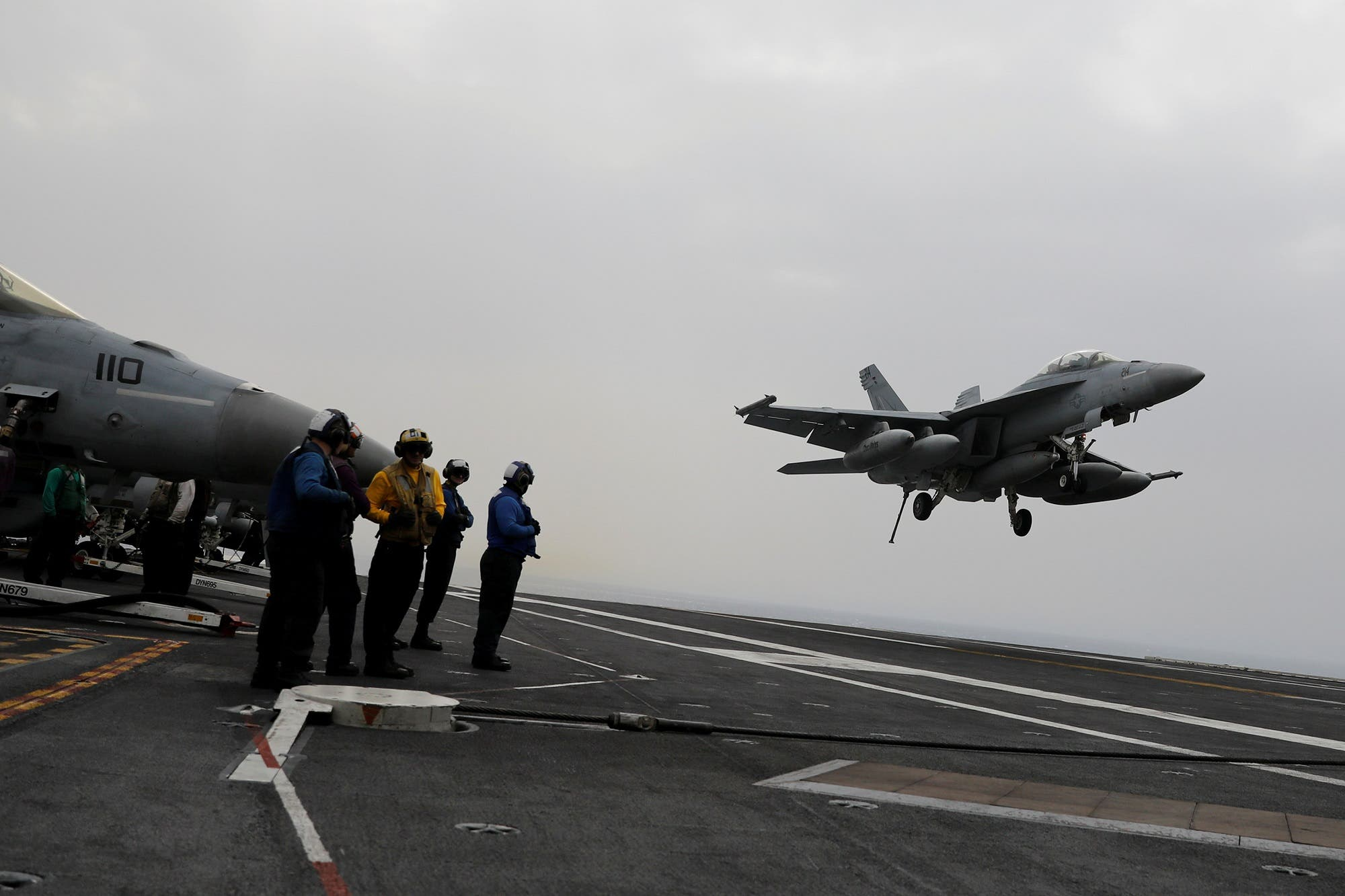 A Navy F/A-18 pilot gestures before taking off from the USS Harry S. Truman aircraft carrier. (Reuters)