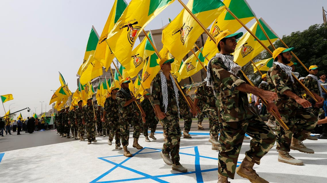 Members of Kata'ib Hezbollah wave party's flags during a parade marking the annual Quds Day, or Jerusalem Day in Baghdad on July 25, 2014. (Reuters)