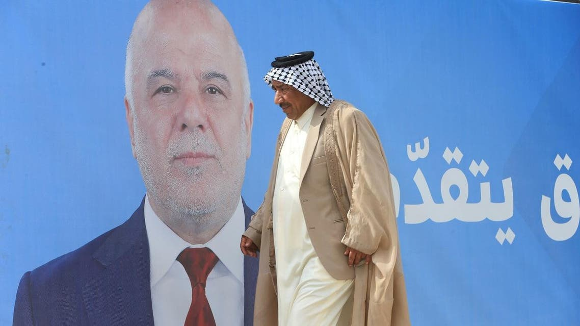 A man walks past a campaign poster of Iraqi Prime Minister Haidar al-Abadi ahead of the parliamentary election, in Najaf. (Reuters)