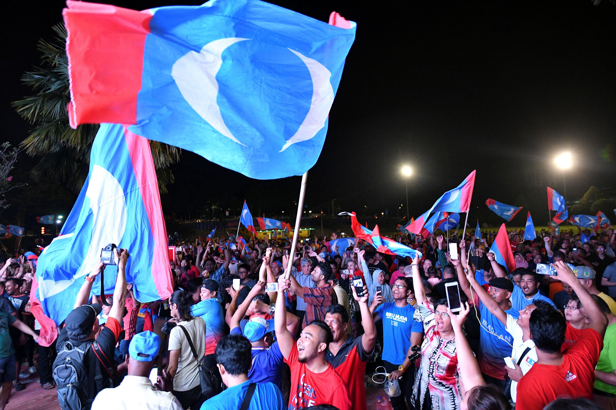 Supporters of Mahathir Mohamad celebrate the victory outside the hotel where he held news conference, in Petaling Jaya, Malaysia, on May 10, 2018. (Reuters)
