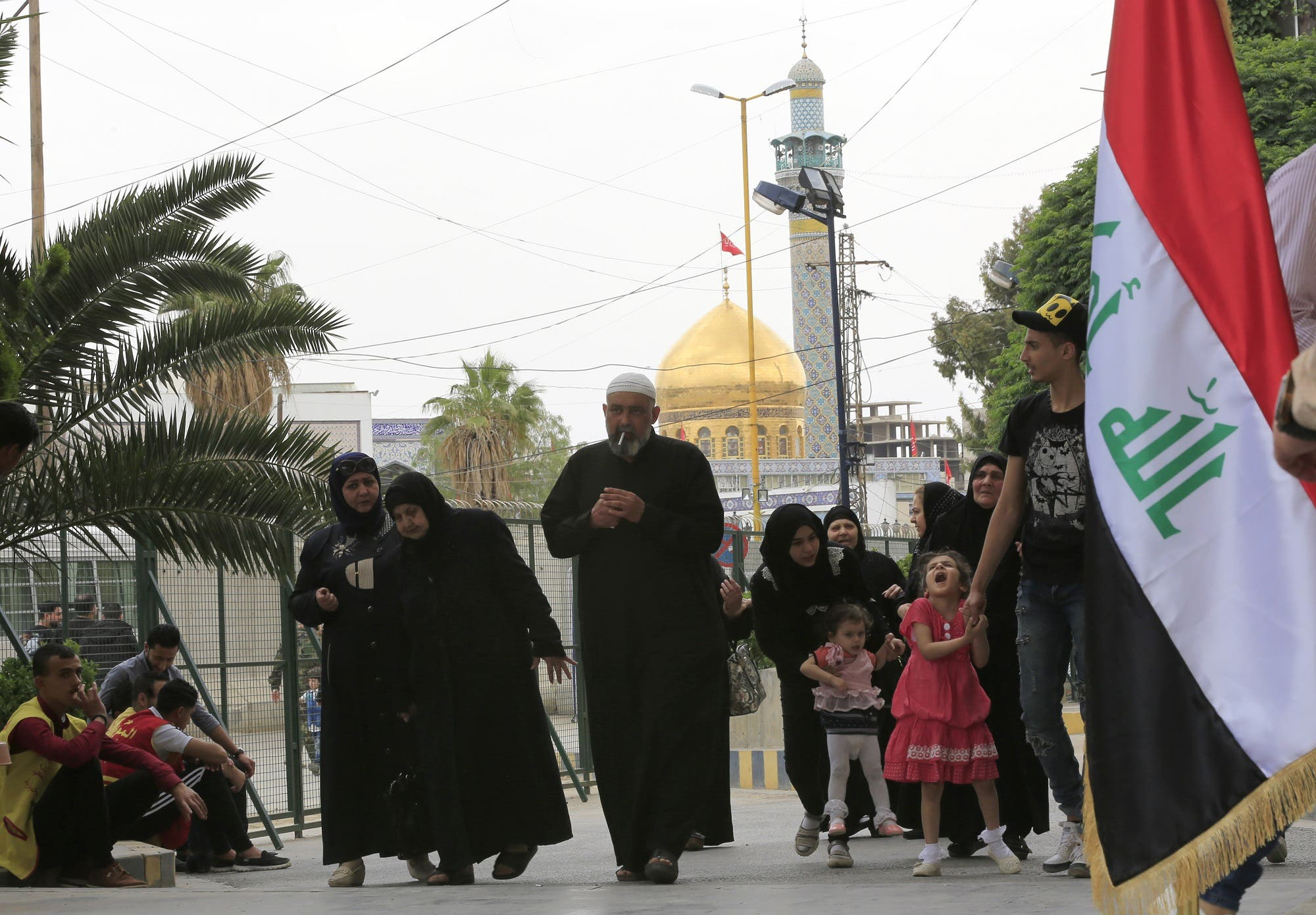 People walk in front of the Sayyida Zeinab mosque on the outskirts of the Syrian capital Damascus on May 10, 2018, as Iraqi residents of Syria vote for the Iraqi parliamentary elections. (AFP)