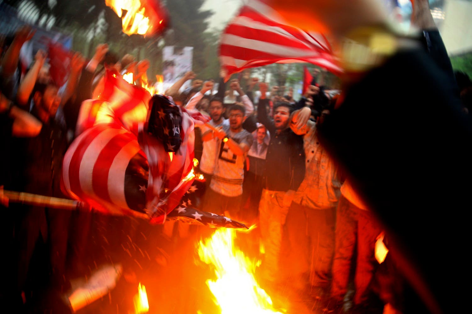 Iranian demonstrators burn representations of the US flag in front of the former US Embassy in Tehran on May 9, 2018. (AP)